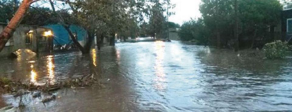 La imagen corresponde a una vista general de una de las calles del barrio Villa Elvira, cubierta de agua que desbordó del arroyo Maldonado.