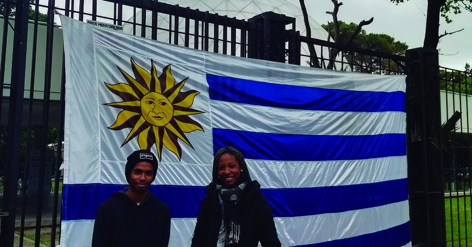 La imagen corresponde a dos estudiantes uruguayos que están delante de la bandera de su país, enganchada en las rejas de entrada al Planetario UNLP: Justo antes de iniciar el Congreso CONECTAR.