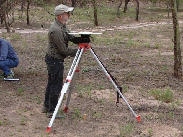 La imagen corresponde al Dr. Daniel Del Cogliano junto a instrumental para mediciones simultáneas GNSS desde tierra. (Es un trípode con una especie de plato en la cima de 1.50m de altura aproximadamente).