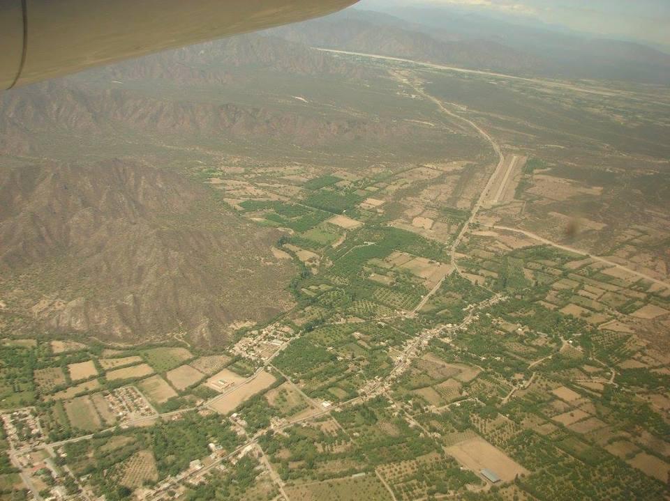 La imagen corresponde a un avista aérea del sitio arqueológico El Shincal. Se observan los restos de las edificaciones, cordones montañosos y parcelas verdes.