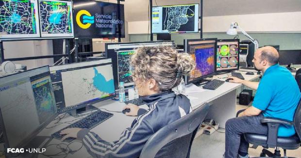 La imagen corresponde a una  oficina del SMN donde una mujer y un hombre están sentados frente a sus respectivas PC. Observan diferentes gráficos e imágenes vinculadas con la meteorología.