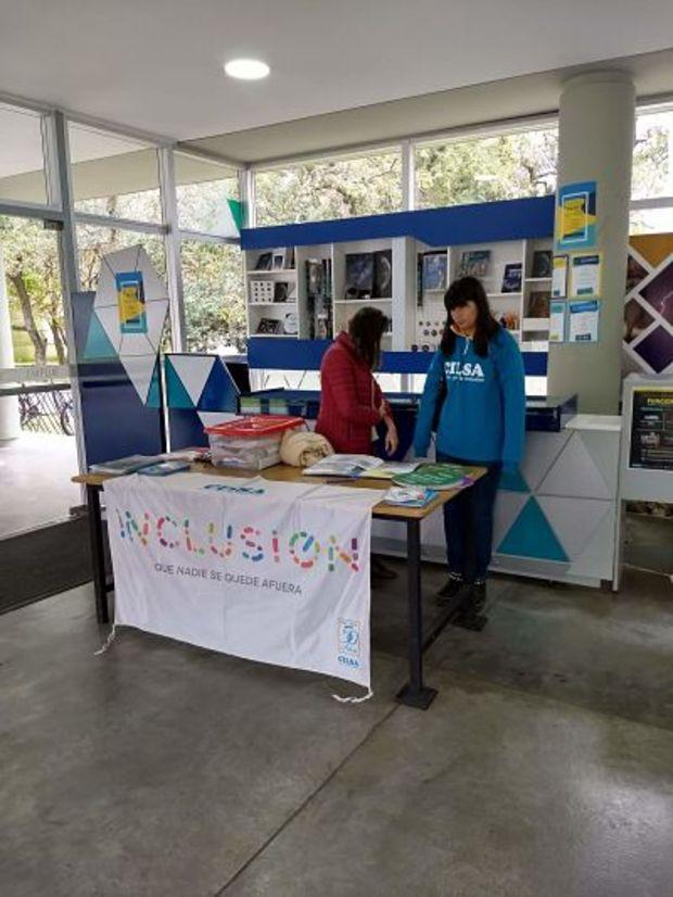 La imagen corresponde al área de merchandising del Planetario donde se colocó una mesa con material informativo de CILSA, el cual es provisto por dos miembros de dicha ONG.
