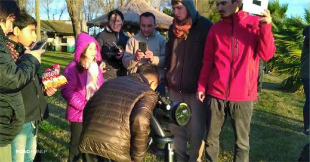 Previo al eclipse, el público practica cómo observar con un telescopio con filtro, junto a estudiantes de FCAG.