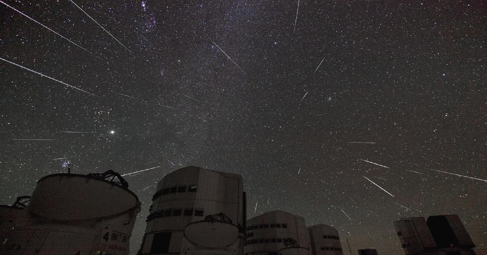 La imagen muestra los edificios del Observatorio Austral Europeo con todo el cielo nocturno atravesado por algunas estrellas fugaces.