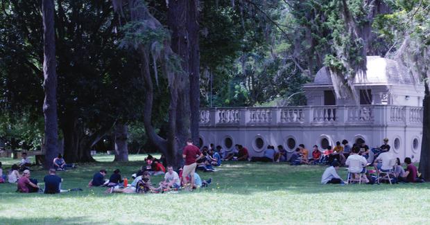 La imagen corresponde a estudiantes en el parque de la FCAG, sentados  en grupos. De fondo, se observa el  Pabellón Geofísico.
