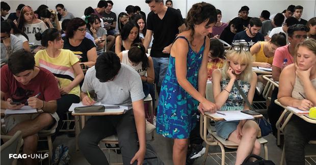 La imagen corresponde a uno de los grupos de ingresantes junto a la docente que está explicando algo a uno de ellos.