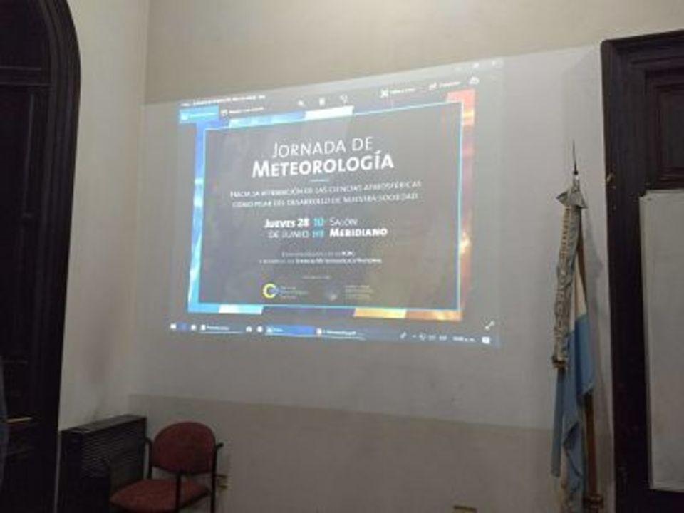 La imagen corresponde a una diapositiva proyectada en la pared del Salón de Actos, que lleva el título de la Jornada. Al costado se observa la bandera argentina que siempre está en el Salón Meridiano de nuestra Facultad.