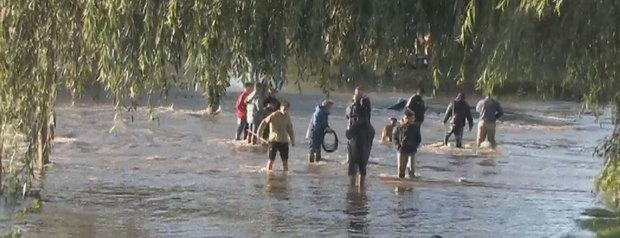 La imagen corresponde a una de las calles inundadas del barrio de Villa Elvira,con un grupo de vecinos con el agua a la altura de sus rodillas.